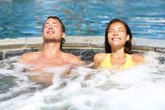 Pares del balneario que se relajan gozando de la tina caliente del Jacuzzi Imágenes de archivo libres de regalías