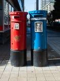 Pares del buzón azules y rojos en la calle imagen de archivo