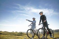 Pares del ciclista con las bicis de montaña que se colocan en la colina debajo del cielo de la tarde y que gozan del sol brillant foto de archivo