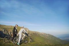 Pares del ciclista con las bicis de montaña que se colocan en la colina debajo del cielo de la tarde y que gozan del sol brillant imagenes de archivo
