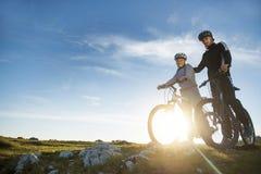 Pares del ciclista con las bicis de montaña que se colocan en la colina debajo del cielo de la tarde y que gozan del sol brillant fotos de archivo libres de regalías
