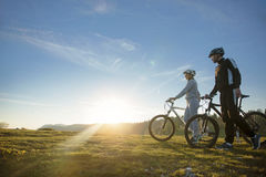 Pares del ciclista con las bicis de montaña que se colocan en la colina debajo del cielo de la tarde y que gozan del sol brillant foto de archivo libre de regalías