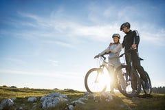 Pares del ciclista con las bicis de montaña que se colocan en la colina debajo del cielo de la tarde y que gozan del sol brillant imagen de archivo