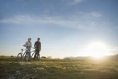 Pares del ciclista con las bicis de montaña que se colocan en la colina debajo del cielo de la tarde y que gozan del sol brillant fotografía de archivo