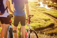 Pares del ciclista que miran en el río abajo del campo Imágenes de archivo libres de regalías