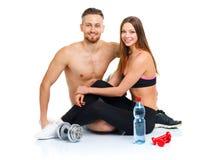 Pares del deporte - el hombre y la mujer después de la aptitud ejercitan con pesa de gimnasia Imagen de archivo