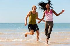 Pares del deporte que activan en la playa Foto de archivo libre de regalías
