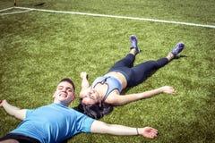 Pares del deporte que mienten en hierba Imagen de archivo libre de regalías