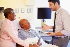 Pares del doctor Talking To Senior en sala Imágenes de archivo libres de regalías
