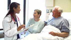 Pares del doctor Talking To Senior en sitio de hospital metrajes