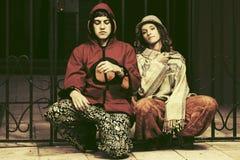 Pares del hippie de la moda de los jóvenes que se sientan en la cerca del hierro Imagen de archivo libre de regalías