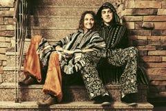Pares del hippie de la moda de los jóvenes que se sientan en los pasos Fotografía de archivo libre de regalías