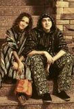 Pares del hippie de la moda de los jóvenes que se sientan en los pasos Imagen de archivo libre de regalías