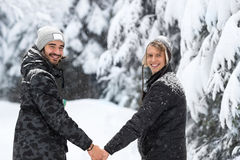 Pares del hombre joven que caminan en la nieve Forest Outdoor Guys Holding Hands foto de archivo