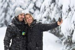 Pares del hombre joven que toman la foto de Selfie en la nieve Forest Outdoor Guys Holding Hands Foto de archivo