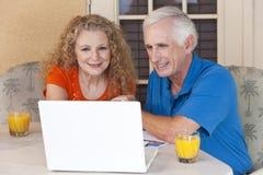 Pares del hombre mayor y de la mujer en el ordenador portátil Imágenes de archivo libres de regalías