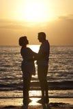 Pares del hombre mayor y de la mujer en la playa en la puesta del sol Fotos de archivo