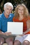 Pares del hombre mayor y de la mujer usando el ordenador portátil Imágenes de archivo libres de regalías