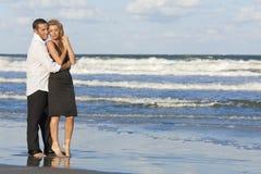 Pares del hombre y de la mujer en abrazo romántico en la playa Foto de archivo libre de regalías