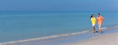 Pares del hombre y de la mujer del panorama que corren en una playa imagen de archivo