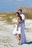 Pares del hombre y de la mujer que recorren en una playa vacía Imagen de archivo libre de regalías