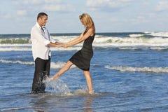 Pares del hombre y de la mujer que tienen baile de la diversión en una playa Imagen de archivo libre de regalías