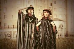Pares del inconformista de la moda de los jóvenes que caminan en una calle de la ciudad Fotografía de archivo libre de regalías