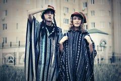 Pares del inconformista de la moda de los jóvenes que caminan en calle de la ciudad Foto de archivo libre de regalías