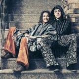 Pares del inconformista de la moda de los jóvenes que se sientan en los pasos Foto de archivo