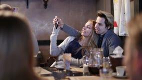 Pares del inconformista que hacen el selfie con el teléfono móvil en café almacen de metraje de vídeo
