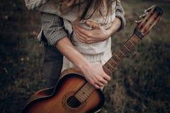 Pares del músico del inconformista que abrazan en el campo, abarcamiento hermoso del hombre Imagen de archivo