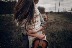 Pares del músico del inconformista que abrazan en el campo, abarcamiento hermoso del hombre Fotografía de archivo libre de regalías