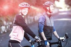 Pares del motorista con la bici de montaña en el camino Fotografía de archivo libre de regalías
