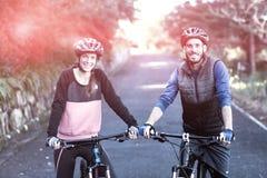 Pares del motorista con la bici de montaña en el camino Foto de archivo libre de regalías