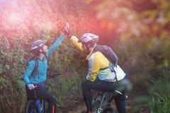 Pares del motorista que dan el alto cinco mientras que monta la bicicleta en campo Fotografía de archivo