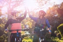 Pares del motorista que dan el alto cinco mientras que monta la bicicleta en campo Fotografía de archivo libre de regalías