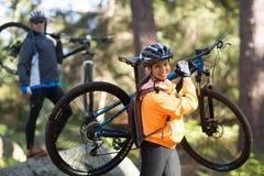 Pares del motorista que sostienen su bici de montaña y que caminan en bosque fotos de archivo