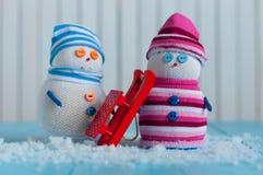Pares del muñeco de nieve hecho a mano con el trineo rojo romántico Fotografía de archivo libre de regalías