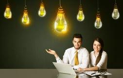 Pares del negocio con los bulbos de la idea Imágenes de archivo libres de regalías