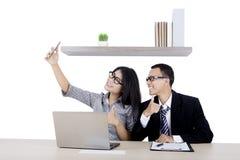 Pares del negocio con smartphone y el pulgar para arriba Foto de archivo libre de regalías
