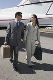 Pares del negocio que caminan junto en el campo de aviación Imagen de archivo libre de regalías