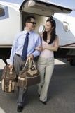 Pares del negocio que caminan junto en el campo de aviación Imagen de archivo