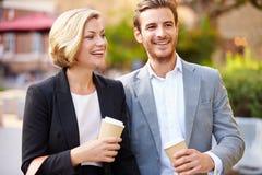 Pares del negocio que caminan a través de parque con café para llevar Foto de archivo