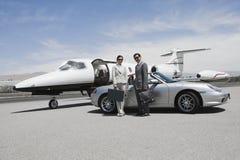 Pares del negocio que se colocan en el jet de Front Of Convertible And Private foto de archivo libre de regalías