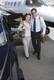 Pares del negocio que se unen en el campo de aviación Imagen de archivo