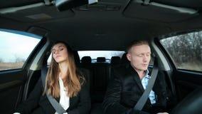 Pares del negocio que trabajan en el coche con el teléfono almacen de video