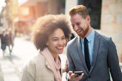 Pares del negocio usando el teléfono elegante al aire libre Imagen de archivo