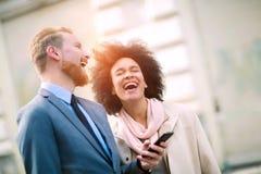 Pares del negocio usando el teléfono elegante al aire libre Foto de archivo