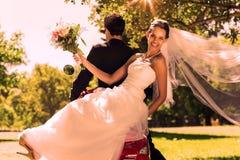 Pares del recién casado que se sientan en la vespa en parque Imágenes de archivo libres de regalías