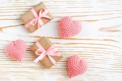Pares del regalo envueltos con la cinta rosada y los corazones hechos punto en un fondo de madera blanco Fotos de archivo libres de regalías